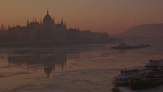 wide angle of the danube river with the hungarian parliament building in the background.  could be dusk. an icy river filled with ice. a barge floats past. several other ferries docked nearby. - budapest video stock e b–roll