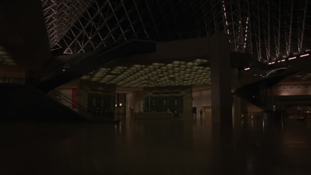 medium angle of underground lobby entrance to museum. see staircases and glass pyramid ceiling. - 1998 stock videos & royalty-free footage