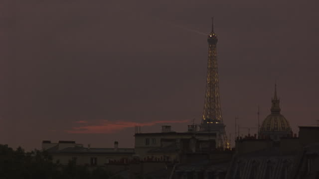 vidéos et rushes de wide angle of paris city skyline. see apartment building rooftops and hotels. light on eiffel tower pans left to right at end of shot. - voiture attelée