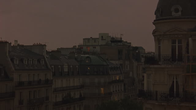 wide angle of paris city skyline. see apartment building rooftops and hotels. dormer windows and balconies visible throughout. - 1998 stock videos and b-roll footage