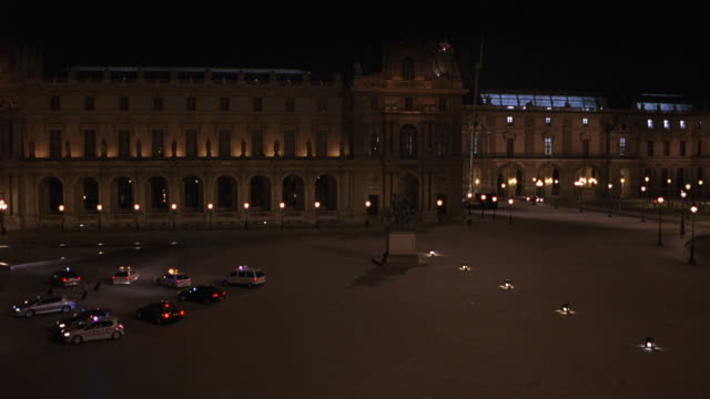 wide angle pan left to right of courtyard of louvre art museum as french police cars drive away with their lights flashing. eiffel tower visible in bg. baroque architecture. could be used for police chase. - 1998 stock videos and b-roll footage