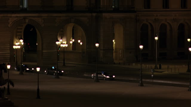 wide angle pan right to left of several french police cars with flashing lights. cars drive across courtyard to entrance of louvre art museum and park. lamp posts line sidewalk. baroque architecture. could be used for a louvre or museum break in. - 1998 stock videos & royalty-free footage