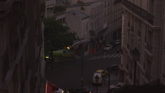 HIGH ANGLE DOWN OF PARISIAN STREETS BETWEEN MULTI-STORY BUILDINGS. BUILDINGS HAVE SMALL BALCONIES. 19TH CENTURY ARCHITECTURE. COULD BE HOTELS OR APARTMENTS. PEDESTRIANS WALKING ON STREETS BELOW. PARKED CARS, PERSON ON BICYCLE. SMALL SHOPS ON STREET CORNER