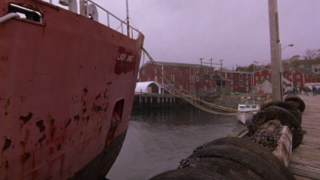 medium angle of a fishing boat  tied to the dock or pier, a small town or fishing village of multi-story red buildings behind it. could be used for new england. - anno 1983 video stock e b–roll