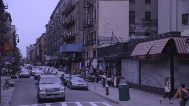 wide angle of nyc street. urban area. fire escapes line apartment buildings. shops with awnings. could be lower class area. cars, trucks, and vans drive down crowded street. pedestrians. cars parked on curb. could be alley. pedestrians walk on sidewalk an - grand central station manhattan stock videos & royalty-free footage