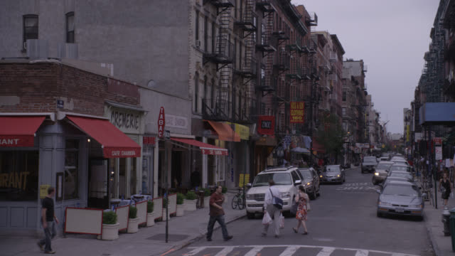 wide angle of nyc street. urban area. fire escapes line apartment buildings. shops with awnings. could be lower class area. cars, trucks, and vans drive down crowded street. pedestrians. cars parked on curb. could be alley. pedestrians walk on sidewalk an - 2000 stock videos & royalty-free footage