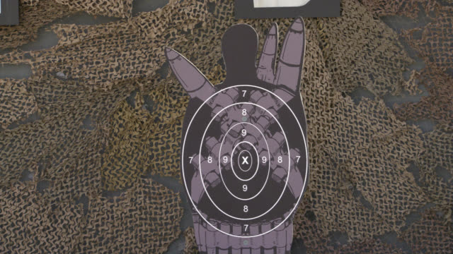 MEDIUM ANGLE OF RIFLE OR GUN RANGE TARGET. TARGET DRESSED LIKE MAN WITH MILITARY WEAPONS. CAMOUFLAGE WALL IN BG. BULLET HOLES OR GUNSHOTS APPEAR IN TARGET.
