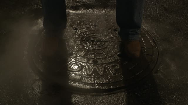 CLOSE ANGLE OF MAN'S FEET STANDING ON MANHOLE COVER. STEAM OR SMOKE RISES FROM SHAKING MANHOLE COVER.