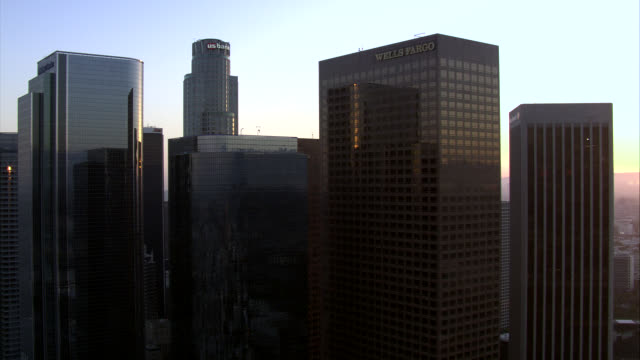 aerial of downtown los angeles at sunset. us bank tower, wells fargo building, gas company tower, paul hastings building, citinational bank, aon, citi, kpmg tower, and pacific telephone microwave tower. high rises, skyscrapers, and glass office buildings. - microwave tower stock videos and b-roll footage