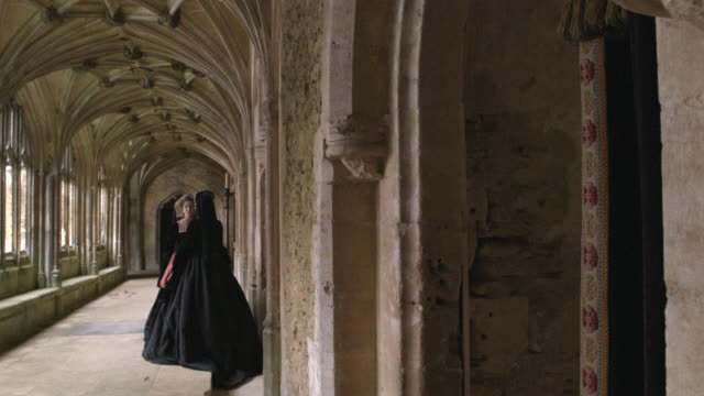 medium angle of hallway or walkway in castle or church. vaulted ceilings. women conversing as man in robes walks by. women wear dresses and gable hood or spanish hood. stone arch ways. renassiance period. - 19th century stock videos & royalty-free footage