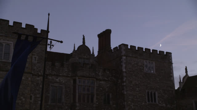 medium angle of knole castle in sevenoaks, kent. could pass for tower of london. stone castle. banner or flag in fg. moon in bg. - tower of london stock videos and b-roll footage