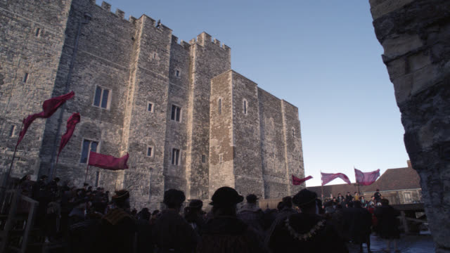 wide angle of crowd of upper class people in courtyard. renaissance nobility or gentry. stone building with crenellation or castle in bg. could be tower of london, actually dover castle. could be for execution or public trial. - 1983年点の映像素材/bロール