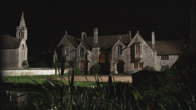 "zoom in on window of upper class house or mansion. could be estate. chapel or church. pond in fg. manor house in great chalfield, wiltshire, england. countryside.<p><a href=""https://www.sonypicturesstockfootage.com/footage?kid=4310"">for day-night matching - 1985 stock videos & royalty-free footage"