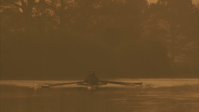 medium angle of team of male  rowers in row boat, shell, or fine boat rowing in river or lake toward camera. could be a men's college university rowing or sculling team.  sun reflects off water as oars dip into water. - mann theaters stock videos & royalty-free footage