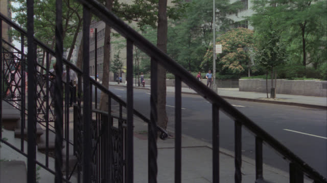 PAN RIGHT TO LEFT FOLLOWING MAN GETTING OUT OF CAR AND WALKING UP STAIRS TO MULTI-STORY BROWNSTONE OR BRICK ROW HOUSES OR APARTMENTS. CITY STREET IN FG. MIDDLE CLASS. RESIDENTIAL AREA. POV THROUGH METAL OR IRON RAILING.