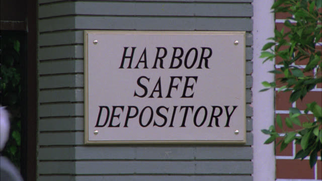 close angle of sign for harbor safe depository. est small brick office building. neg cut. could be used as a medical center. city street. - small office stock videos & royalty-free footage
