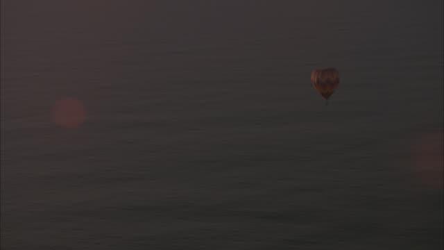 vídeos de stock e filmes b-roll de aerial circling around multi-colored  hot air balloon over calm water, ocean. - territórios ultramarinos franceses