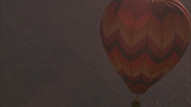 vídeos y material grabado en eventos de stock de aerial circling around hot air balloon over calm dark blue ocean. lens flare from sun. gold glare off water from sun, breakpoint in ocean water. could be underwater reef. people in basket. - territorios franceses de ultramar