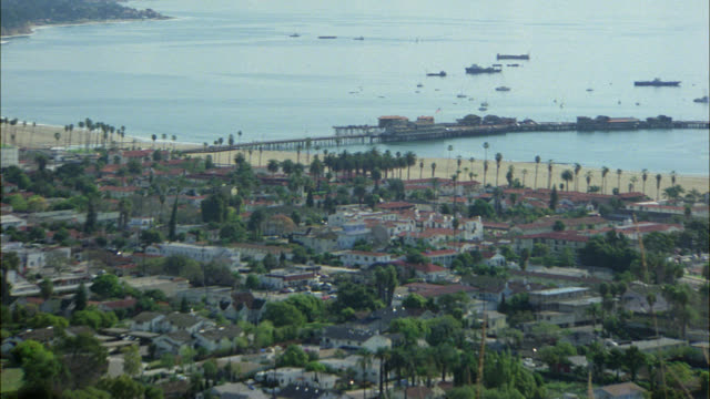 PAN RIGHT TO LEFT FROM TOP OF HILL OF  SANTA BARBARA PIER, COASTLINE WITH SHIPS IN OCEAN TO CITYSCAPE, RESIDENTIAL AREA SURROUNDED BY MOUNTAINS. CARS DRIVING ON FREEWAY. CITIES.