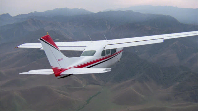 stockvideo's en b-roll-footage met aerial tracking of private single engine  propeller plane, could be cessna flying over desert mountains. matching r942-2 r942-3 - propeller