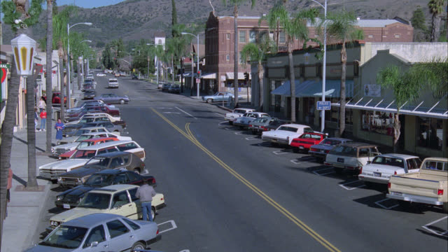vídeos y material grabado en eventos de stock de high angle down of main street in small town. commercial or shopping area. cars parked on both sides of the street. could be downtown burbank. mountains in bg. - puerta giratoria