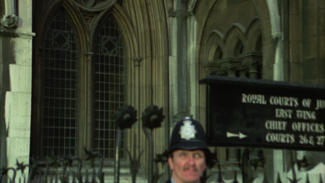 """zoom in from police office or guard standing in front of building with sign that reads """"royal courts of justice"""" to arched windows on building. courthouse. london. government buildings. - royal courts of justice stock videos & royalty-free footage"""