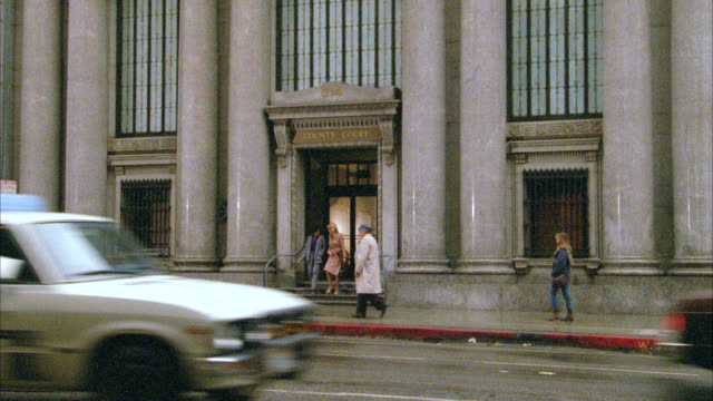 wide angle of people walking on sidewalk and out of courthouse. cars driving by in fg. cities. street wet from the rain. - 1982 stock videos and b-roll footage