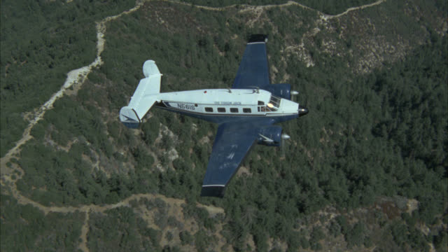 aerial air-to-air tracking shot of small airplane over mountains.  road winds through mountains. passenger plane. twin engine propeller. blue and white. - propeller video stock e b–roll