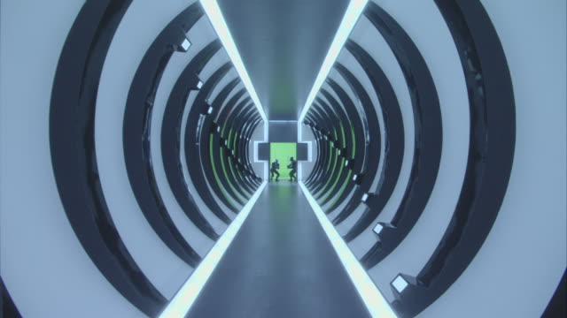 medium angle of futuristic circular hallway. see path or walk way leading to door at end of hallway in shape of cross. see concave struts or supports on either side of hallway walls, neon blue lights on supports designed in a spiral pattern. see door at e - cancello video stock e b–roll