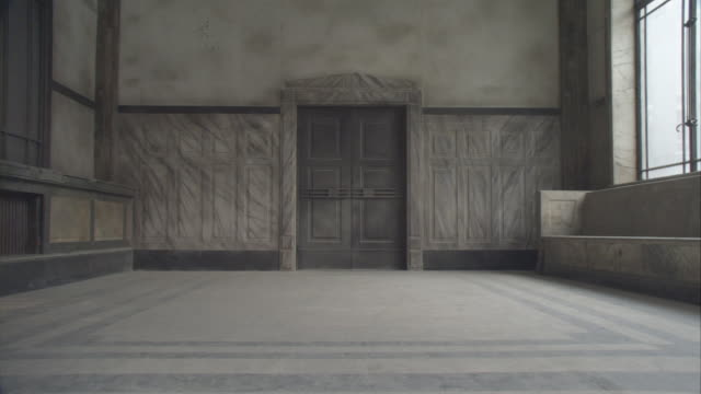 medium angle of doorway or entrance to courtroom or government building or old building. see tiled floor, wooden bench to right of frame, large doorway frame center, and large desk or table frame right. see window above bench frame left allowing sunlight - fade out 個影片檔及 b 捲影像