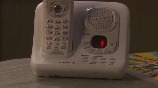 pull back from cordless telephone. see number buttons and led display. could be speaker phone in office, house, home office, or restaurant. answering machines. - cordless phone stock videos and b-roll footage