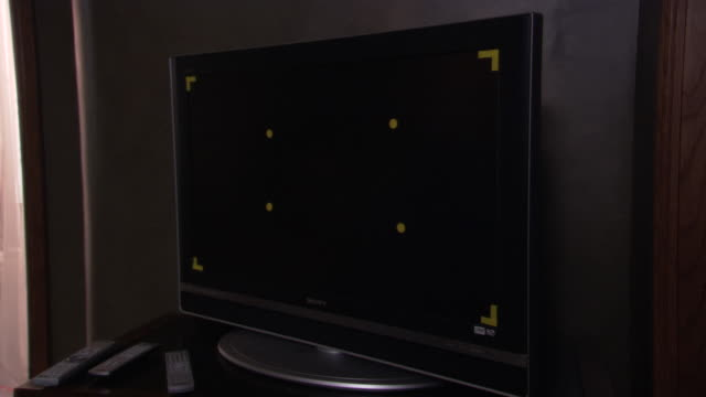 medium angle of black flat screen television. see yellow grid stickers on television screen. see no image on television. camera is tilted left. - black entertainment television stock videos & royalty-free footage