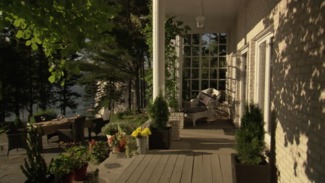 medium angle of outside terrace or patio. see black patio furniture on left. see stone concrete. see vases of pink and yellow  flowers in foreground. see multiple pine trees in foreground. see cumulus clouds in blue sky. see lake in background. - great lakes stock videos & royalty-free footage