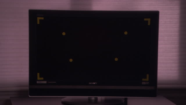 "MEDIUM ANGLE OF EMPTY BLACK TELEVISION SCREEN OR COMPUTER MONITOR. SEE FLAT SCREEN TELEVISION WITH ""SONY"" SIGN. SEE YELLOW MARKINGS ON SCREEN. SEE WINDOW SCREENS OR BLINDS BEHIND MONITOR."