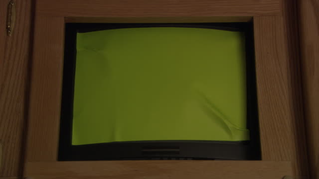 MEDIUM ANGLE OF TELEVISION OR COMPUTER SCREEN, MONITOR, OR DISPLAY. SCREEN IS COMPLETELY GREEN OR COVERED IN GREEN SCREEN. SEE BLACK DESKTOP MONITOR, DIGITAL DISPLAY, OR LCD WITH WOODEN FRAME.