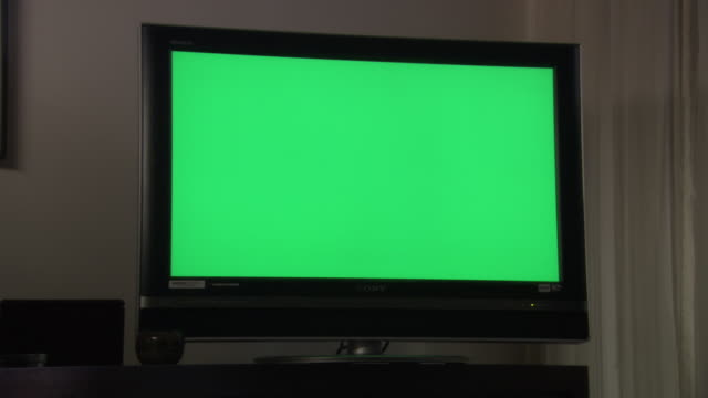 medium angle of television screen or monitor with completely green display. could be computer screen, monitor, digital display, or lcd. monitor sits on shelf or entertainment center. - device screen stock videos & royalty-free footage
