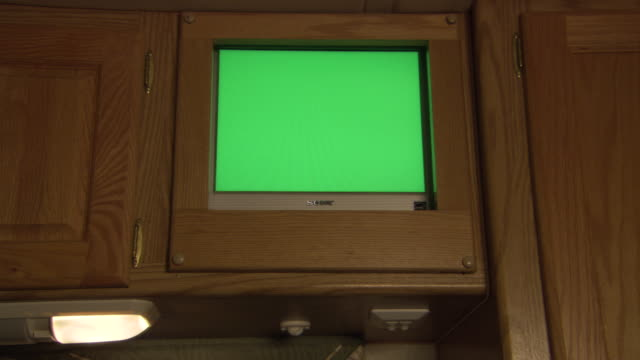 medium angle of silver sony television sitting inside of wooden cabinet. could be in kitchen. television monitor or screen is totally green. - tv screen stock videos and b-roll footage