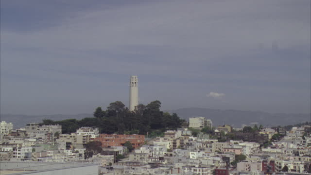 medium angle of coit tower from a distance. see multi-story buildings surrounding coit tower. - north beach san francisco stock videos and b-roll footage