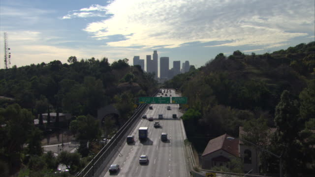 HIGH ANGLE DOWN ON 110 FREEWAY OR HIGHWAY TOWARDS DOWNTOWN. SEE LOS ANGELES SKYLINE IN BACKGROUND. SEE DECIDUOUS TREES. SEE SKY WITH CIRRUS CLOUDS.