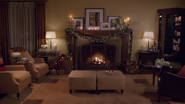 vídeos de stock, filmes e b-roll de wide angle of upper class house living room, chairs, fireplace with fire, framed photographs, ottomans, christmas decoration on mantle. lamps, bookshelves. pan up at end of clip. - decoração de natal