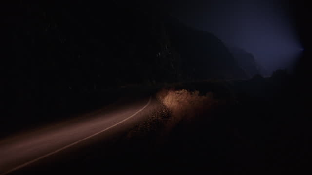 wide angle of red or maroon car driving on winding two lane road or highway through fog at bottom of cliffs. could be in wilderness, rural area. 12 fps. - santa clarita stock videos & royalty-free footage