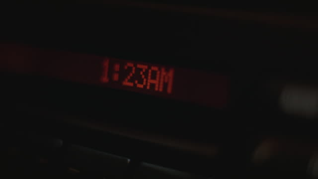 "CLOSE ANGLE OF DIGITAL CLOCK READING ""1:23 AM"". COULD BE ON ALARM CLOCK, RADIO OR CD PLAYER."