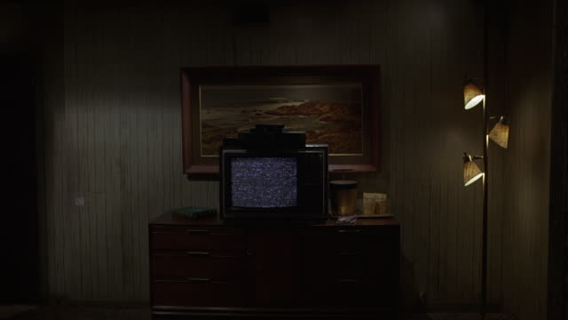 wide angle of television set with static on top of bureau in lower class motel room.  dingy room has lamp and painting, ice bucket next to tv. burn-ins. - television static stock videos & royalty-free footage