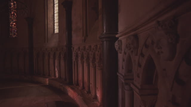 medium angle of church wall. short marble etchings decorate wall in a column-like fashion. stained glass windom in bg. - natural column stock videos and b-roll footage