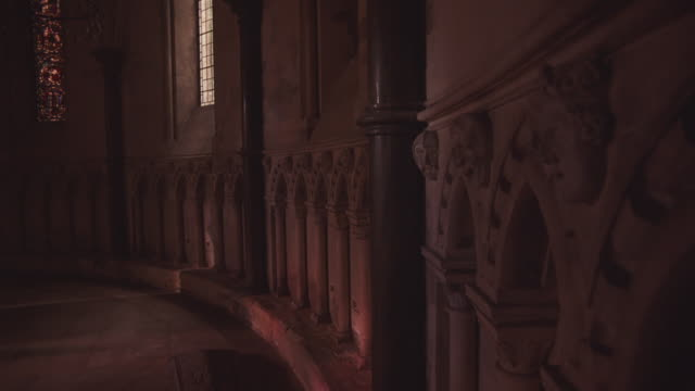 medium angle of church wall. short marble etchings decorate wall in a column like fashion. see stained glass windom in bg. - marble wall stock videos and b-roll footage