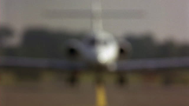 vidéos et rushes de wide angle of private jet taxiing on runway, tarmac towards pov. airplane turns off and pack of european police cars are seen chasing plane with bizbars, sirens, lights flashing. plane is hawker siddeley hs 125-700b. police action. 21 fps. - piste d'envol