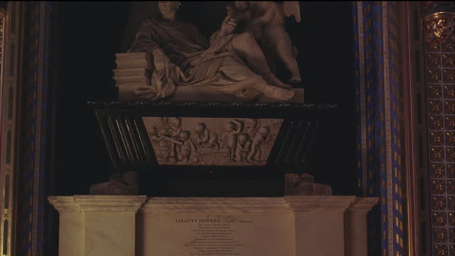 MEDIUM ANGLE OF ISAAC NEWTON'S TOMB AT WESTMINSTER ABBEY. STATUE OF NEWTON, FRIEZE AND PLAQUE DECORATE TOMB. MONUMENTS. MATCHING SHOT WITH 3169-030. 3 FPS.