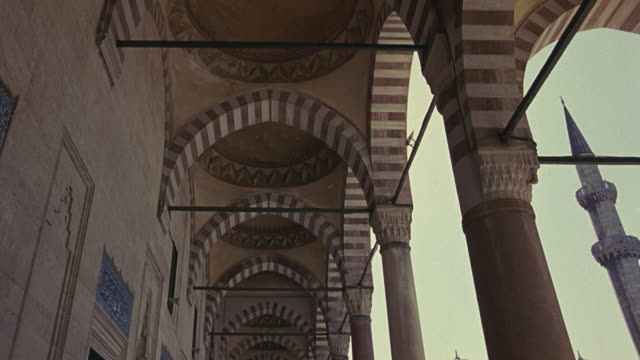 UP ANGLE OF STRIPED POINTED ARCHES AND CEILING. COULD BE SULEYMANIYE MOSQUE. ISLAMIC ARCHITECTURE.