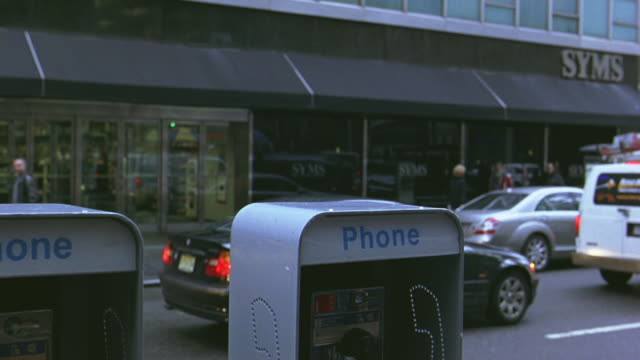 """medium angle of pay phones along city street. """"syms"""" clothing store across street. cars stopped. - pay phone stock videos and b-roll footage"""