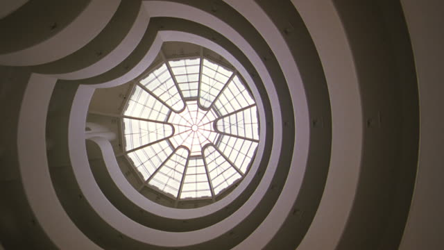 up angle of guggenheim museum ceiling, skylight, atrium. sunlight shining through skylight.  floors of museum visible on sides. architecture. frank lloyd wright. art museum. - museum stock videos & royalty-free footage